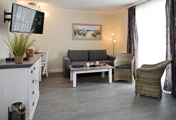 Wohnbereich mit Doppelschlafcouch und Flachbild-TV
