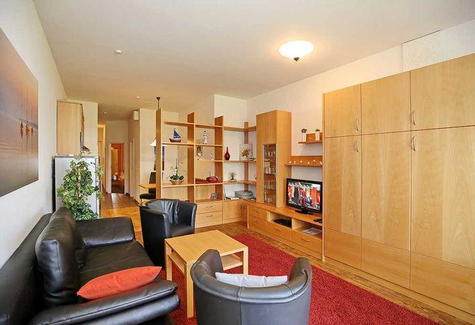 Wohnbereich mit Sofa, Schrankbett und Flachbild-TV