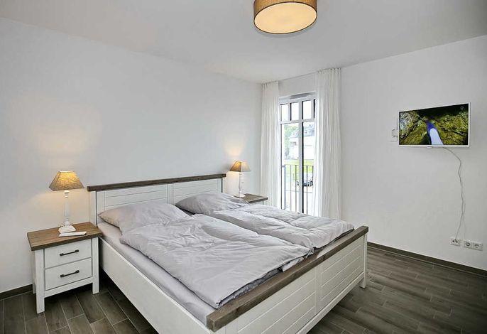 erstes Schlafzimmer mit Doppelbett und Flachbild-TV