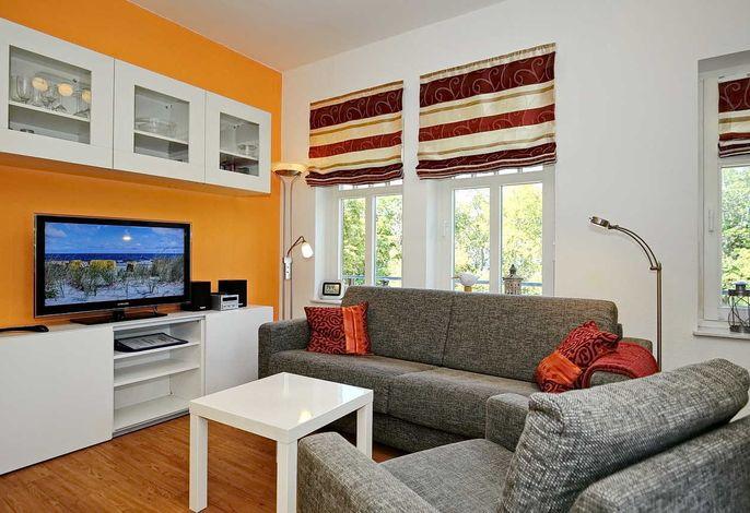 Wohnbereich mit Schlafcouch und Flachbild-TV