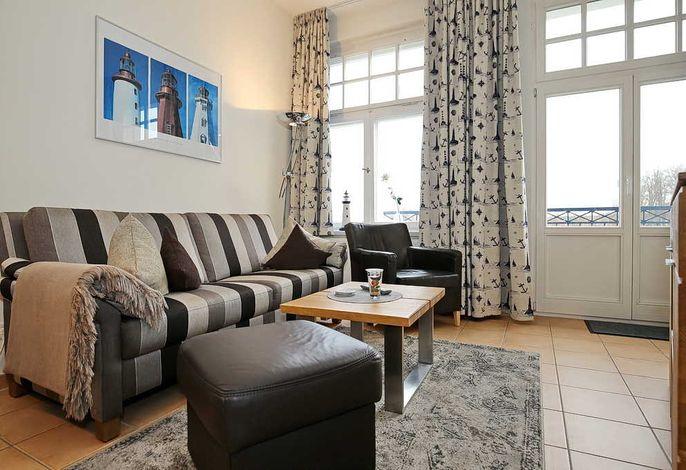 Wohnbereich mit Sofa, Sessel und Balkon