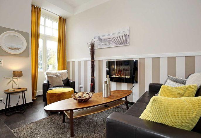 Wohnbereich mit Couch und Elektrokamin