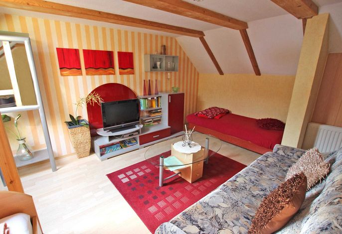 Wohnzimmer mit Couch und zwei Einzelbetten