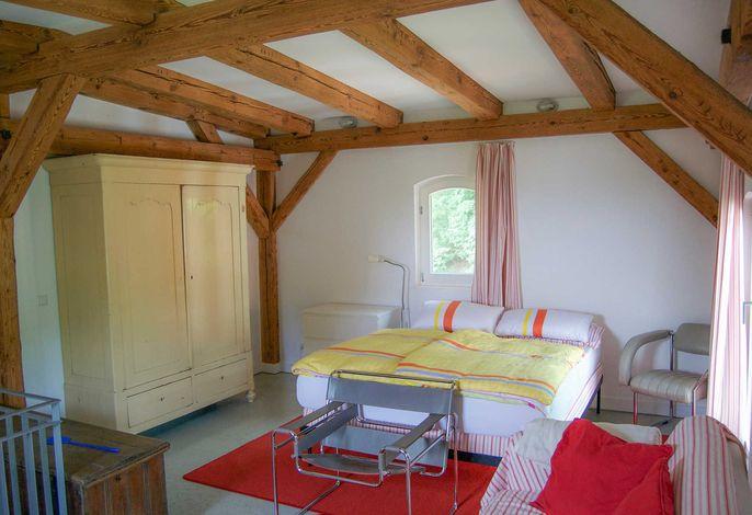 Schlafbereich mit Doppelbett und großem Schrank im Obergeschoss
