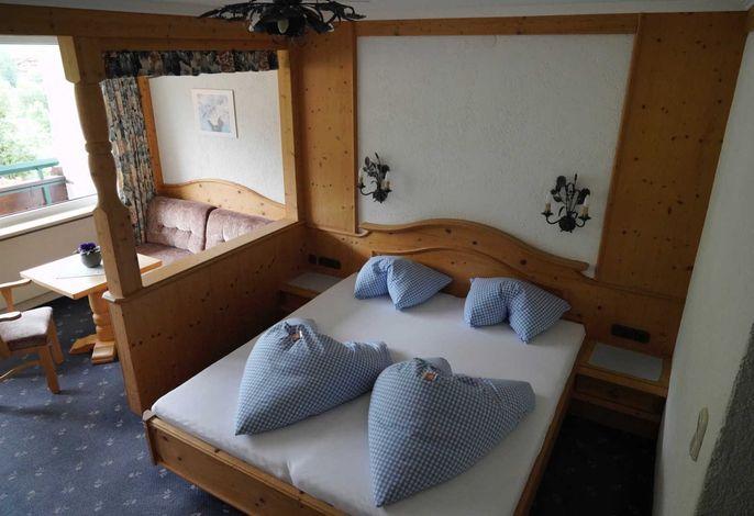 Schlafzimmer mit Couchecke und Balkon