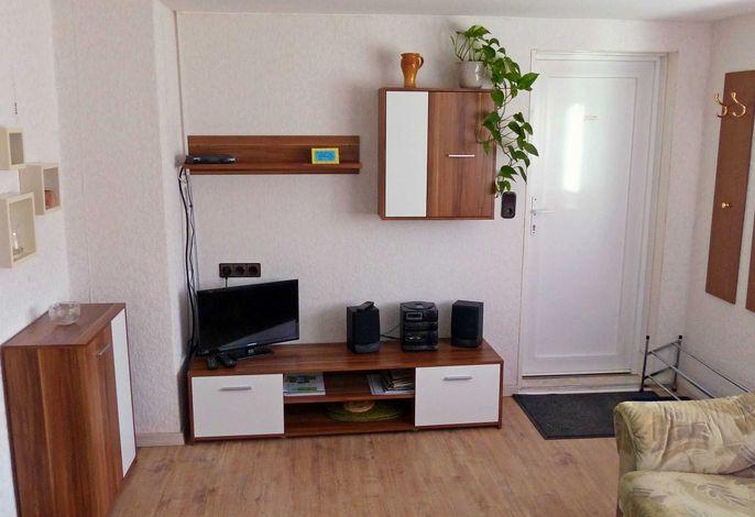 Wohnwand mit TV und Garderobe am Eingang