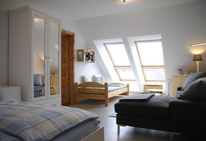 heller freundlicher Wohn-/Schlafbereich, große Fenster mit Ostseefernblick