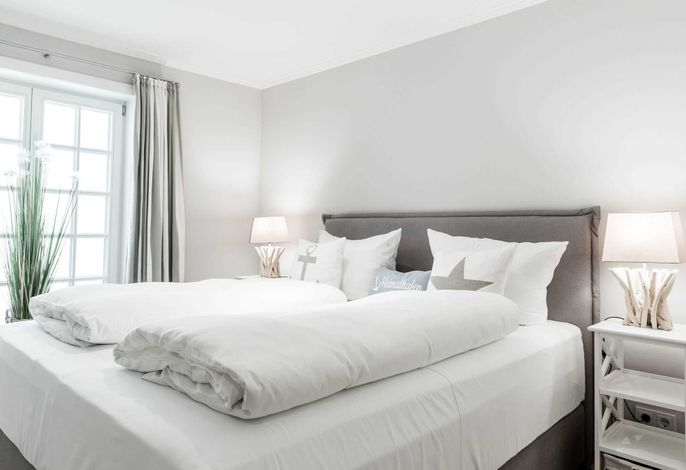 Schlafzimmer im Untergeschoss mit Doppelbett und eigenem Badezimmer im Mittelweg 10 in Wenningstedt auf Sylt.