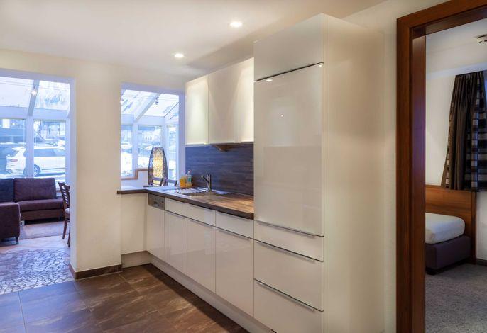 Küchenbereich mit Blick auf den Wohn-/Essbereich im Wintergarten