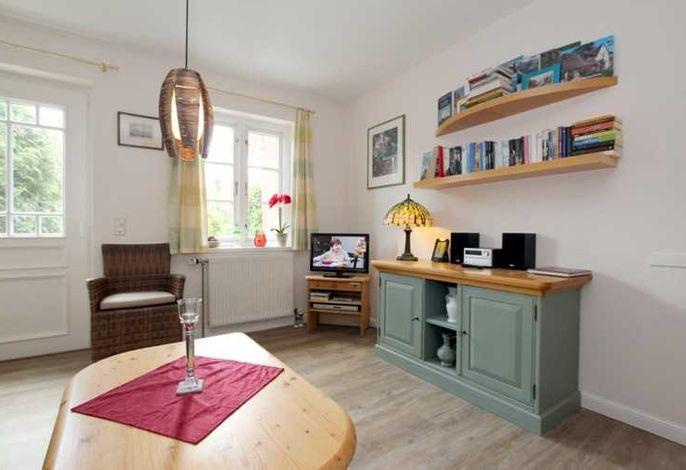 Wohnzimmer mit TV und Zugang zur eigenen Terrasse