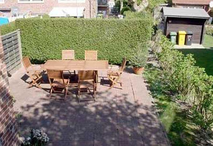 Sonnige Sitzecke auf der Terrasse neben dem Hauseingang