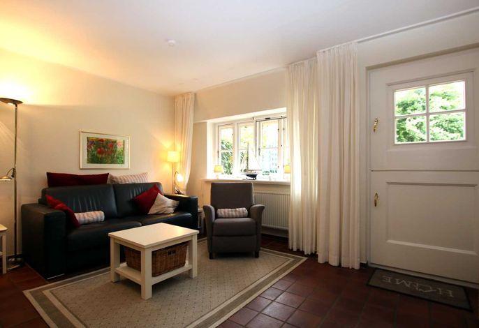 Gemütliche Sitzecke mit Zugang zur Terrasse und Blick auf den Fernseher und Kamin