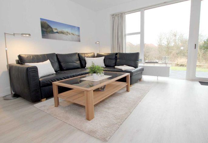 Helles Wohnzimmer mit gemütlicher Sitzecke und Ausgang zur eigenen Südwestterrasse
