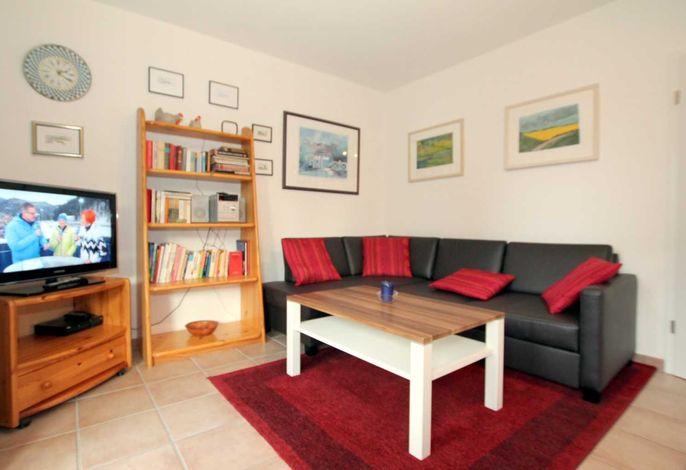 Wohnzimmer mit gemütlicher Sitzgelegenheit und Flat TV