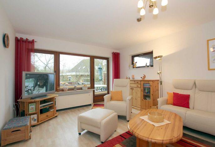 Helles, freundliches Wohnzimmer mit großem Flat-TV und direktem Ausgang zur eigenen Terrasse