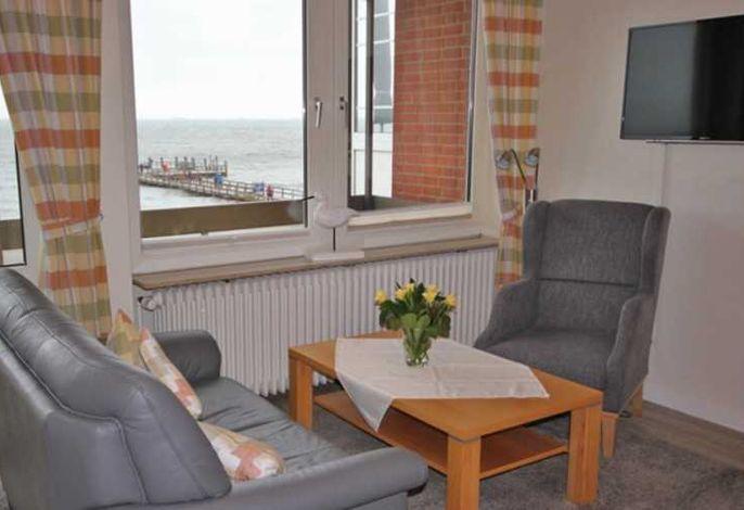 Ein Blick in das helle Wohnzimmer mit Zugang zum Balkon