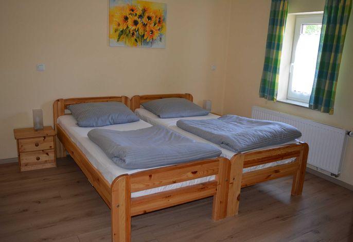 Doppelbett 1,80x2,00m. Der Wohnraum ist mit Laminat ausgelegt.