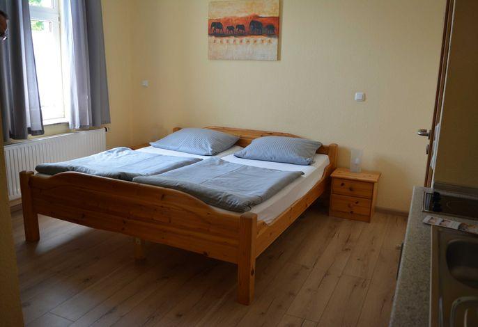 Doppelbett 1,80x2,00m. Der Wohnraum ist mit Laminat ausgelegt