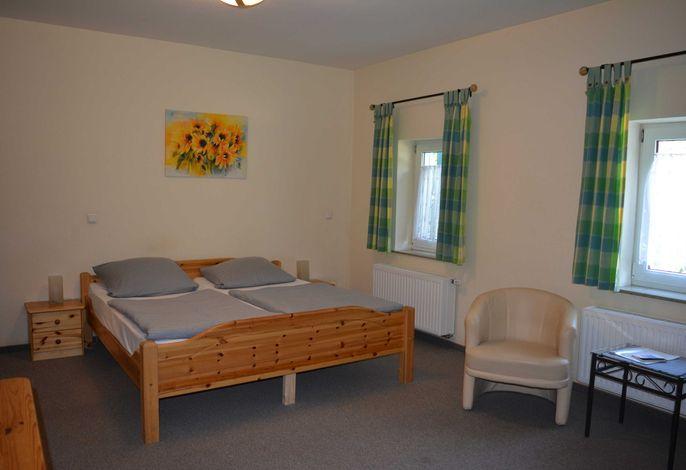 Doppelbett 1,80x2,00m. Der Wohnraum ist mit Teppichboden ausgelegt