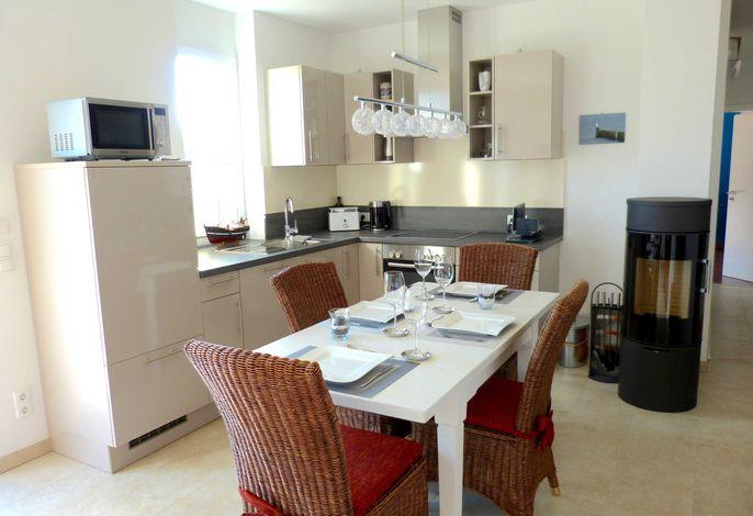 Voll ausgestattete Küche mit Essbereich und Kaminofen