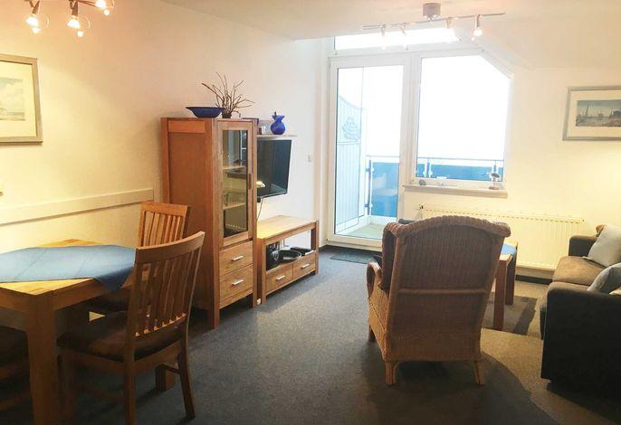 Wohnzimmer mit offener Küchenzeile, Couch, Couchtisch, Schrank sowie Flachbild-TV