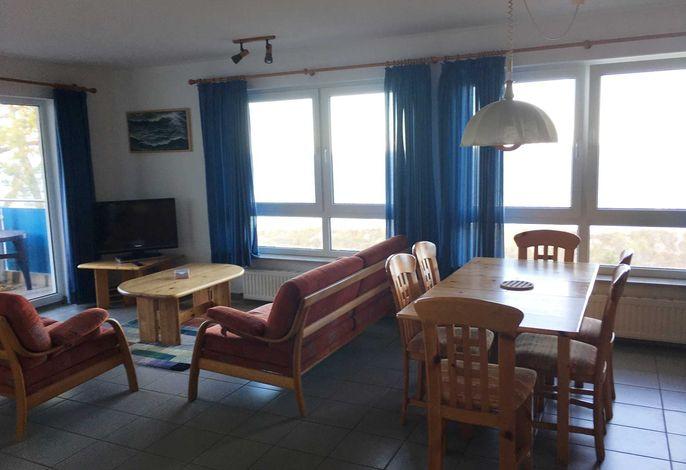 Wohnzimmer mit offener Küchenzeile, Couch, Couchtisch, Schrankwand sowie Flachbild-TV, Tisch mit 6 Stühlen
