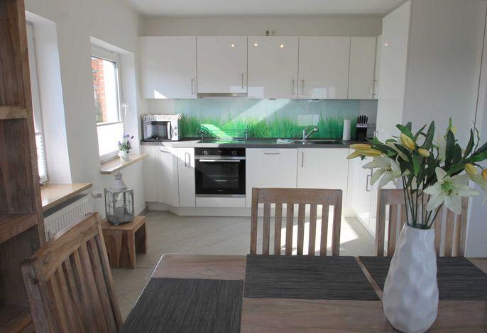 Esszimmer mit offen integrierter sehr gut ausgestatteter Küche