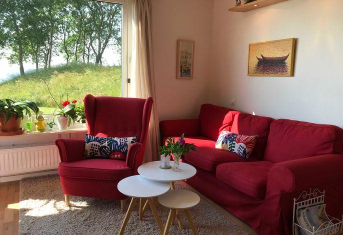 Wohnzimmer mit Meerblick, gemütlicher Couch und Sessel